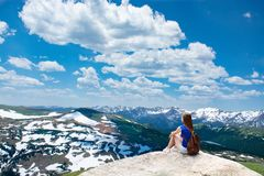 Girl sitting on the rock on hiking trip in beautiful mountains. Snowy peaks and green meadows and hills View from Trail Ridge Road. Rocky Mountains National royalty free stock photo