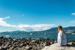 Girl Sitting on a Rock at Kitsilano Beach in Vancouver, Canada Royalty Free Stock Image