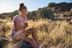 Girl sitting on rock looking at cell Royalty Free Stock Photos