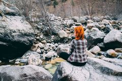 The woman sitting on the rock mountain. The girl sitting on the rock mountain. The girl sitting on the rock mountain , relaxing on the top of the mountain Royalty Free Stock Image