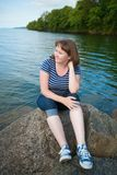 Girl sitting on a rock near the lake Stock Photography