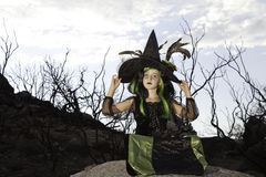 Girl sitting on rock stone holding her witch hat Stock Photography