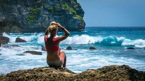 Girl sitting on the Rock and watching Huge Waves hitting Tembeling Coastline at Nusa Penida Island, Bali Indonesia Stock Photos