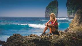 Girl sitting on the Rock and watching Huge Waves hitting Tembeling Coastline at Nusa Penida Island, Bali Indonesia Stock Images