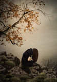The girl sitting on a rock. Young girl with long hair,her head down , sitting on a rock under a tree over water.Autumn loneliness Royalty Free Stock Image