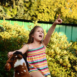 Girl sitting on a rocking horse. Stock Photography