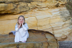 Girl sitting on rocks Royalty Free Stock Photography
