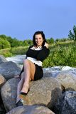 Girl sitting on rocks Royalty Free Stock Image