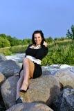 Girl sitting on rocks Royalty Free Stock Image