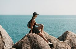 girl sitting on rocks and looking stock photos