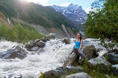 Girl sitting on the rocks in mountain river Stock Photo