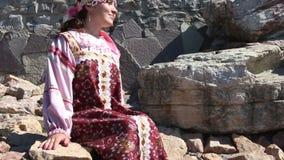Girl sitting on a rocks, Russian folk costume stock video footage