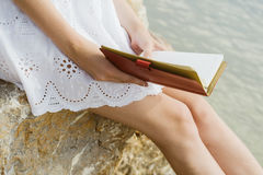 Girl sitting on the rocks by the sea, working with a laptop Royalty Free Stock Photography