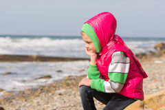 Girl sitting on rocky beach and the sea head on his hand looking to the frame Royalty Free Stock Photography