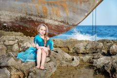 Cute doll girl sitting on the rocky shore of the sea ocean in azure celestial dress near an abandoned boat. Girl sitting on the rocky sea shore in azure dress Stock Images