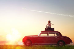 Girl sitting on roof of car. Toward adventure! Girl relaxing and enjoying road trip. Happy child girl sitting on roof of vintage car Royalty Free Stock Photo