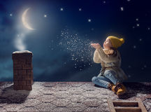 Girl sitting on the roof. Happy child girl playing on a snowy winter walk. Little girl enjoys the game. Child girl sitting on the roof and looking at snowfall Royalty Free Stock Images