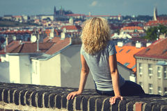 Girl sitting on the roof of a house Royalty Free Stock Photo