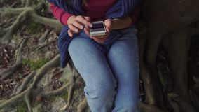 Girl is sitting on the roots and she is using the smartphone. A girl is sitting on the roots and she is using the smartphone. Close up stock video