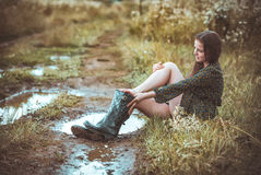 Girl sitting on rural road in time a rain Royalty Free Stock Photos
