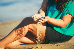 Girl sitting on sand at the beach. In her open palms sand that pours through her fingers Stock Photo
