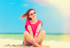 Girl sitting on the sand Stock Photos