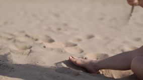 A girl is pouring sand through her fingers. Sand in the girl`s hand. stock video