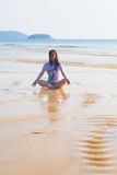 Girl sitting on the sand by the ocean. Royalty Free Stock Photography