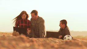 Girl sitting on the sand and two men working for laptops slow motion video. Evening at sunset on the sand sitting woman and two men are working enthusiastically stock footage