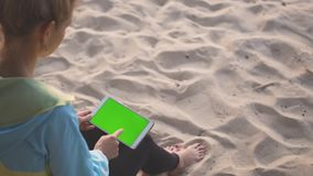 A girl sitting on the sand and using a tablet with chroma key screen. Swiping. A girl sitting on the sand and using a tablet with chroma key screen. Scrolls the stock video footage