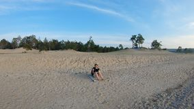 Girl sitting on the sandy beach and drawing a landscape. Gimbal shot. 4K stock footage