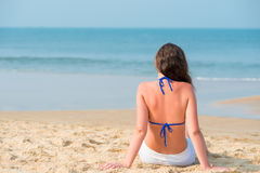 Girl sitting on the sandy beach Royalty Free Stock Photography