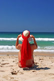 Girl sitting on sandy beach in the sun adjusting hat. Blue sky, blue sea red scarf. Spain. Stock Image