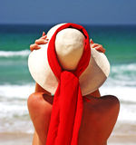 Girl sitting on sandy beach in the sun adjusting hat. Blue sky, blue sea red scarf. Spain. Attractive, tanned girl sitting on sandy beach in the sun adjusting Stock Photos