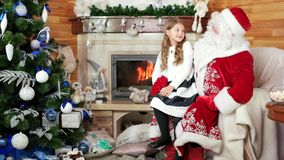 Girl sitting at santa lap, happy kid telling papa noel his christmas wishes, smiling young lady stock video footage