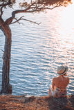 Girl sitting by the sea at sunset Stock Photography