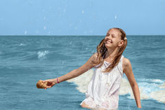 Girl sitting in sea surf on the beach Royalty Free Stock Photography