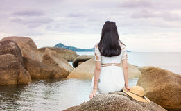 Girl sitting on the seaside rocks Stock Images