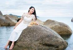 Girl sitting on the seaside rocks. Fashionable girl sitting on the seaside rocks Stock Photos