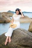Girl sitting on the seaside rocks. Fashionable girl sitting on the seaside rocks Royalty Free Stock Photography