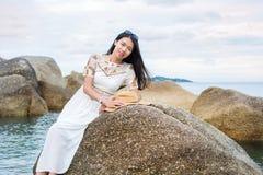 Girl sitting on the seaside rocks. Fashionable girl sitting on the seaside rocks Royalty Free Stock Photos