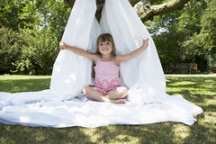Girl Sitting In Sheet Tent In Backyard Royalty Free Stock Photo