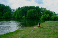 Girl sitting on the shore of lake Stock Photos