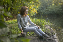 Girl sitting on the shore of the lake. At sunset Stock Images