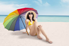 Girl sitting at shore under umbrella Stock Images