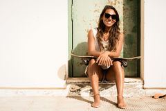 Girl sitting with a skateboard in front of grunge door. Royalty Free Stock Image