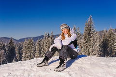 Girl sitting on ski slope. Girl in winter clothes sitting on ski slope in winter in mountains Royalty Free Stock Photography