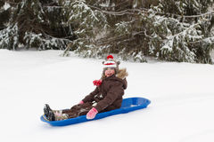 Girl sitting sledding toboggan sled snow winter Royalty Free Stock Image