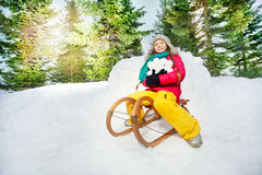 Girl sitting on the sledge and holding snowballs Royalty Free Stock Photography