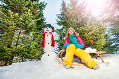Girl sitting on sledge with snowman at the forest Royalty Free Stock Photos